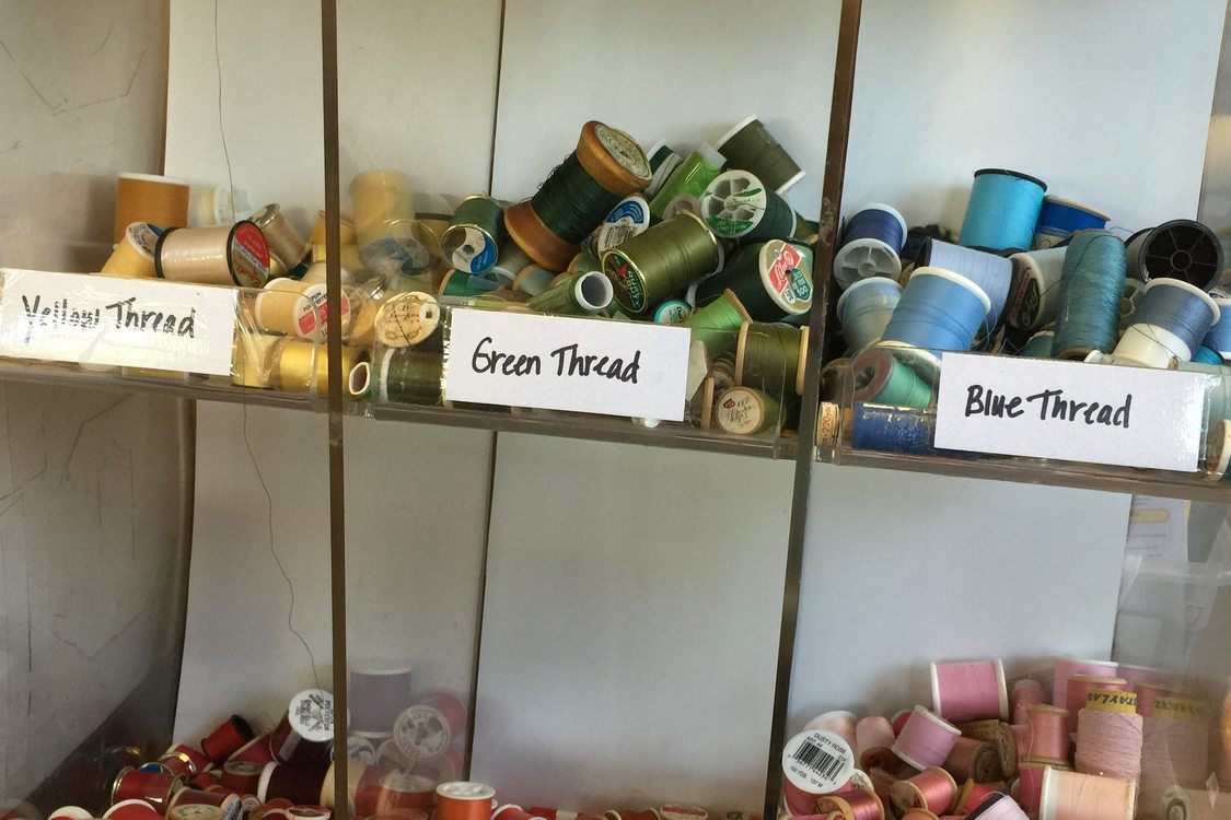 storage bins of used thread sorted by color