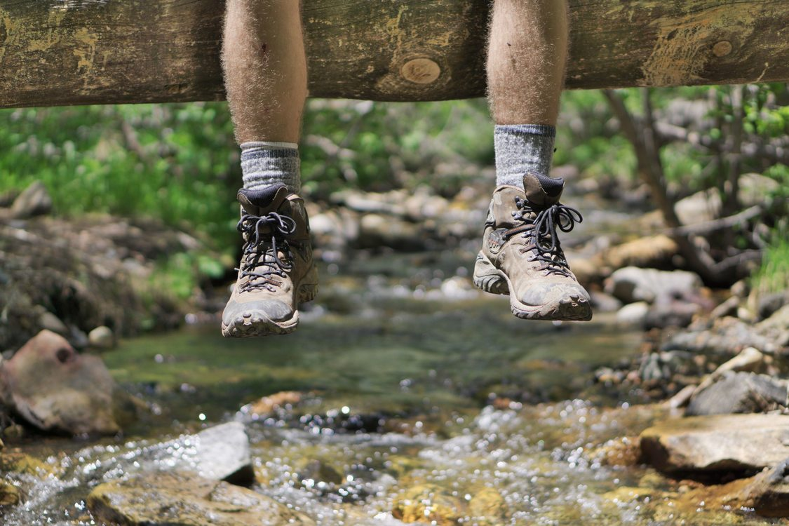 photo of feet dangling from log
