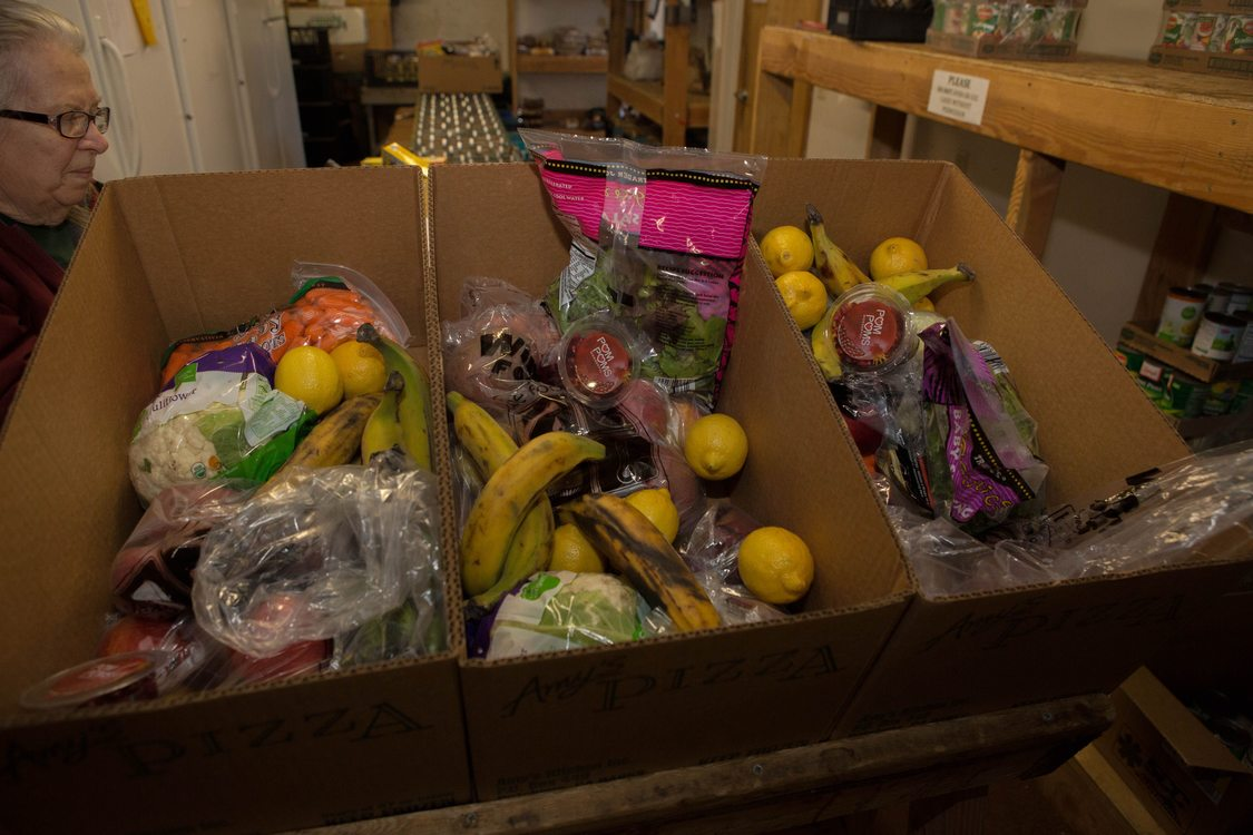 Volunteer Joyce Rollins packs food boxes with fresh fruit and vegetables