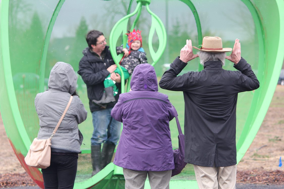 visitors enjoy apple art structure at Orenco Woods Nature Park