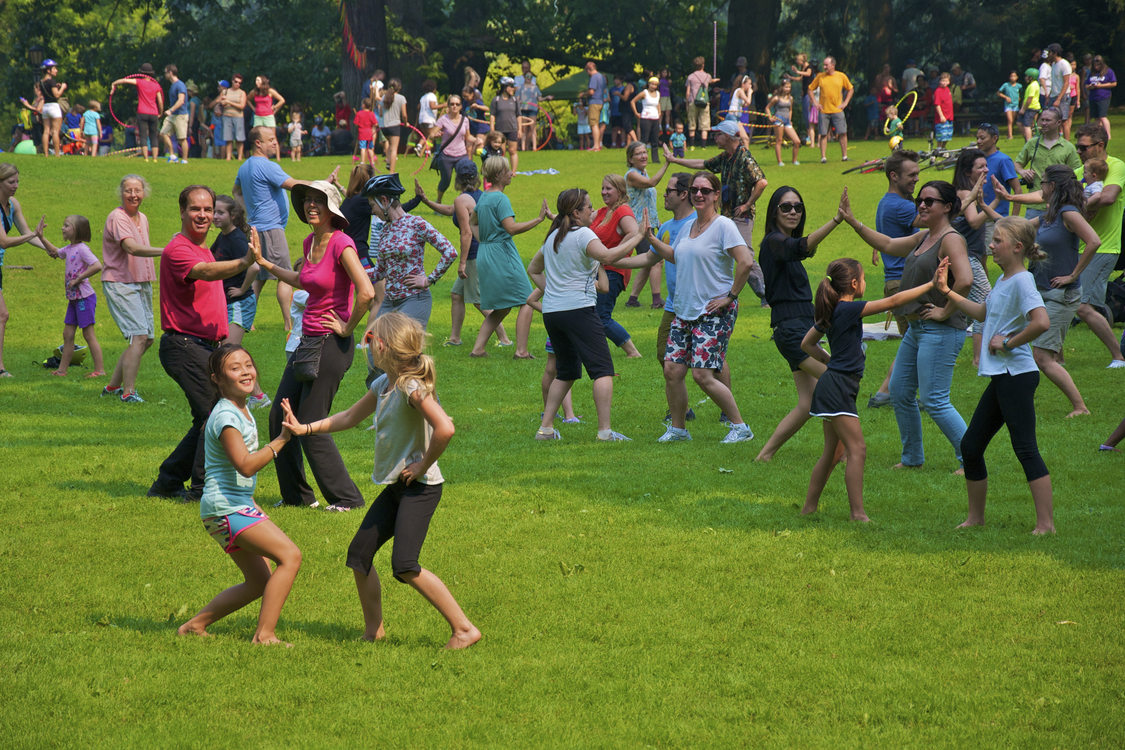 photo of men, women and children dancing in grassy area at Sunday Parkways