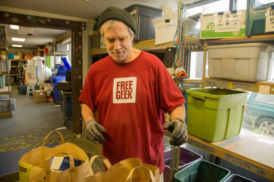 employee of Free Geek sorting through bags of donated electronics