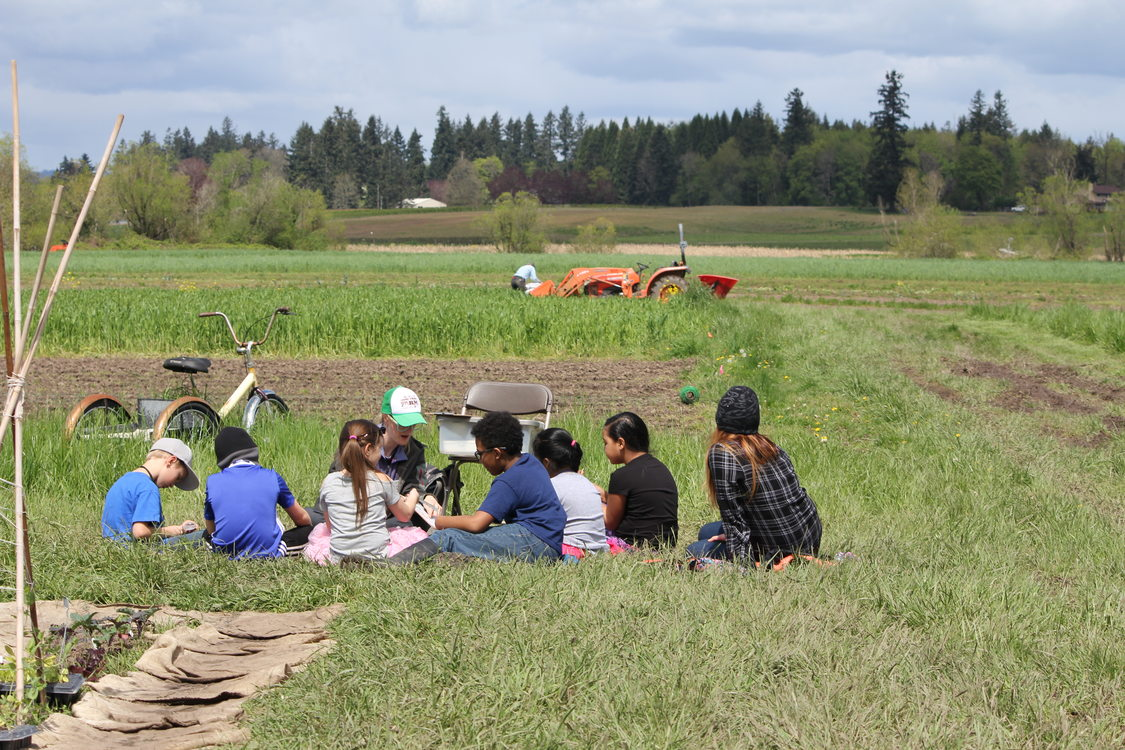 children sitting in a grassy field at Sauvie Island Center