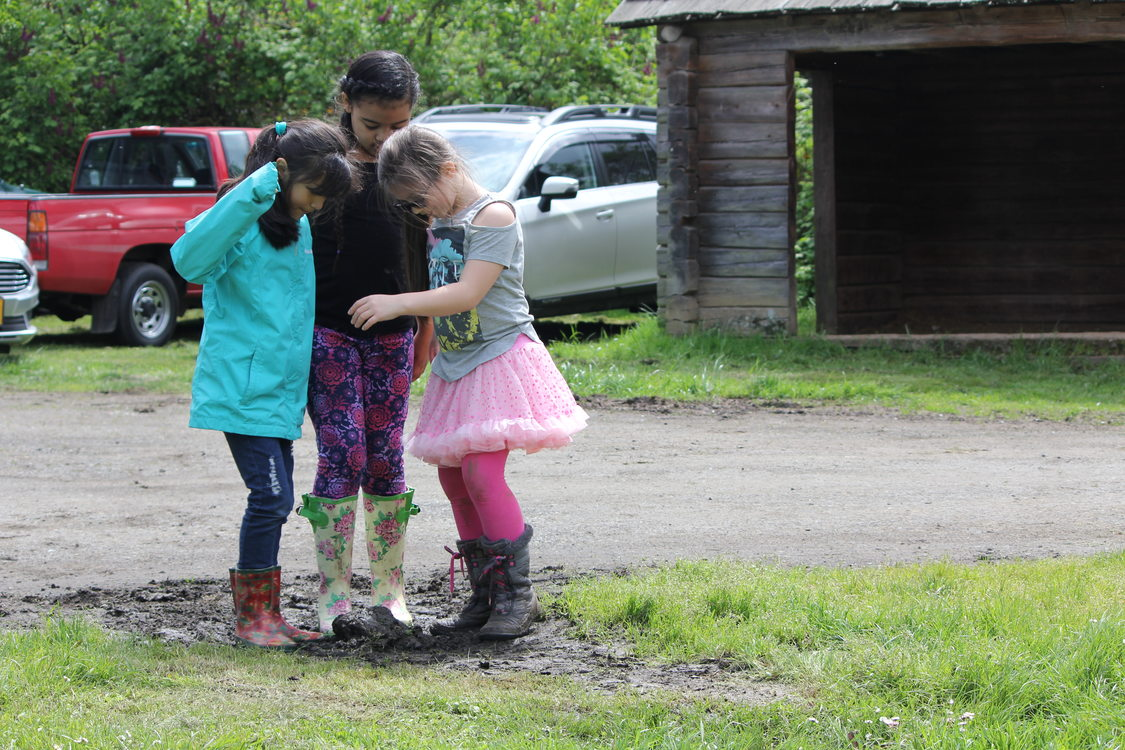three children in boots gather together at Sauvie Island Center