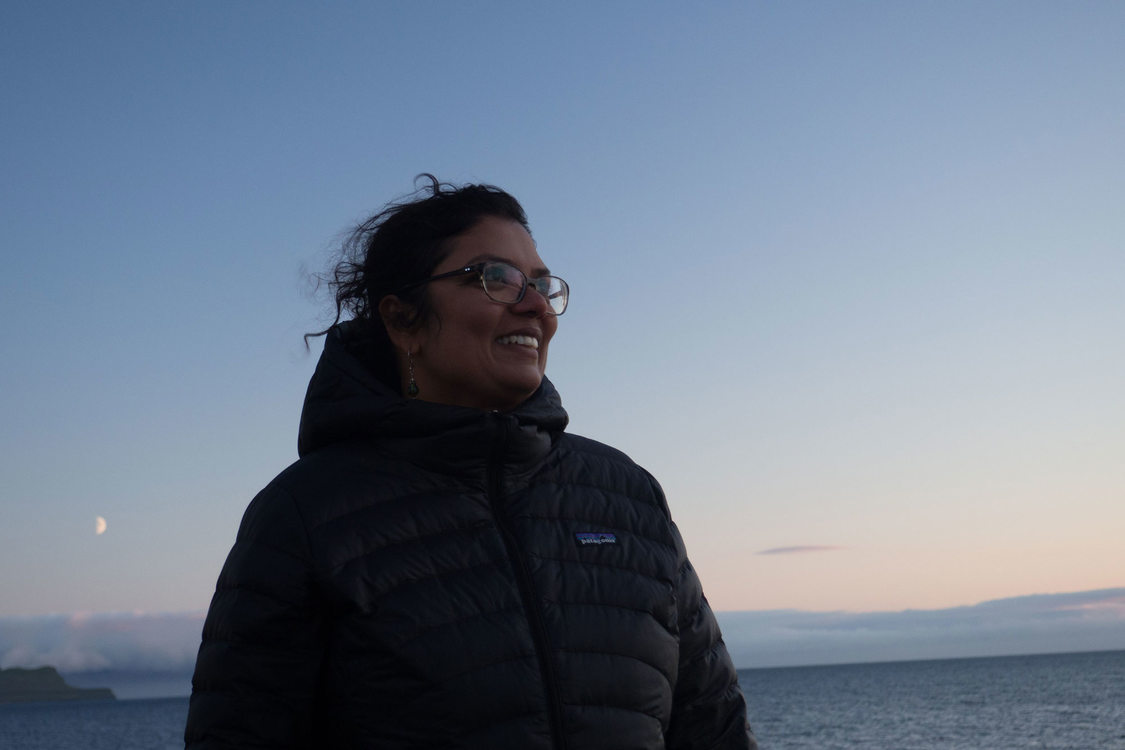 Raahi Reddy standing on a windy beach at dusk.