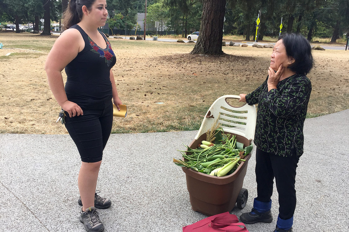 woman with a plastic cart full of vegetables speaking with another woman in Nadaka Nature Park