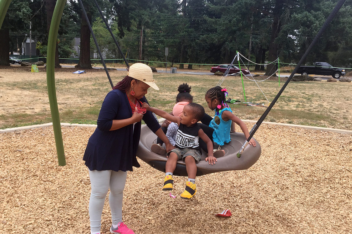 grandmother pushing her four grandchildren on a swing at Nadaka Nature Park