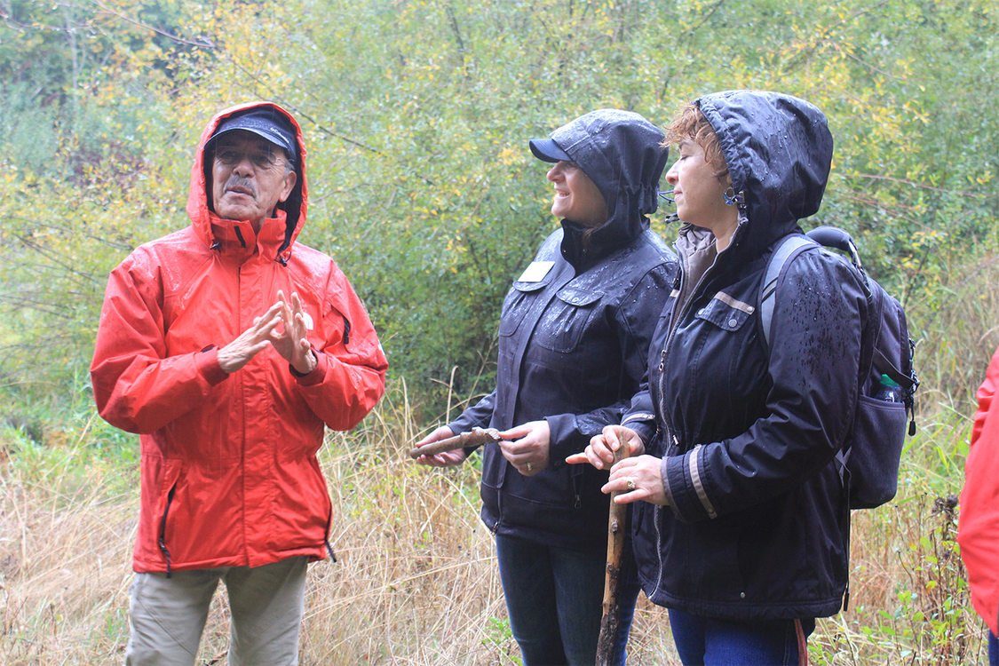 man in red jacket speaks to two women on a rainy day at the future Chehalem Ridge Nature Park