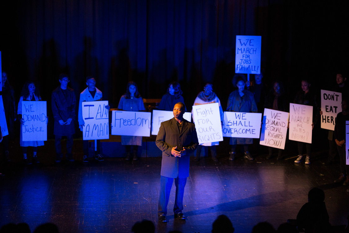 "Actors on stage recreating the March on Washington and Dr. Martin Luther King, Jr.'s ""I have a dream speech.""  Actors hold signs that say ""freedom"" ""we shall overcome"" ""fight for our rights"" and more."