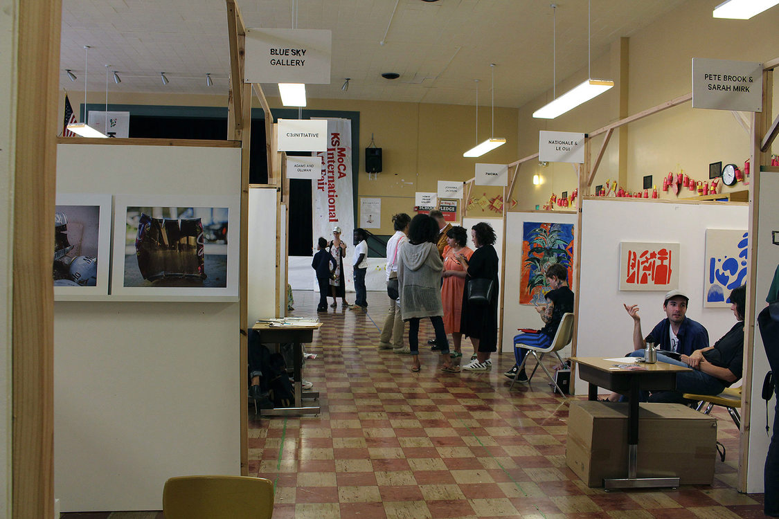 an art fair in a school cafeteria with individual artist booths set up