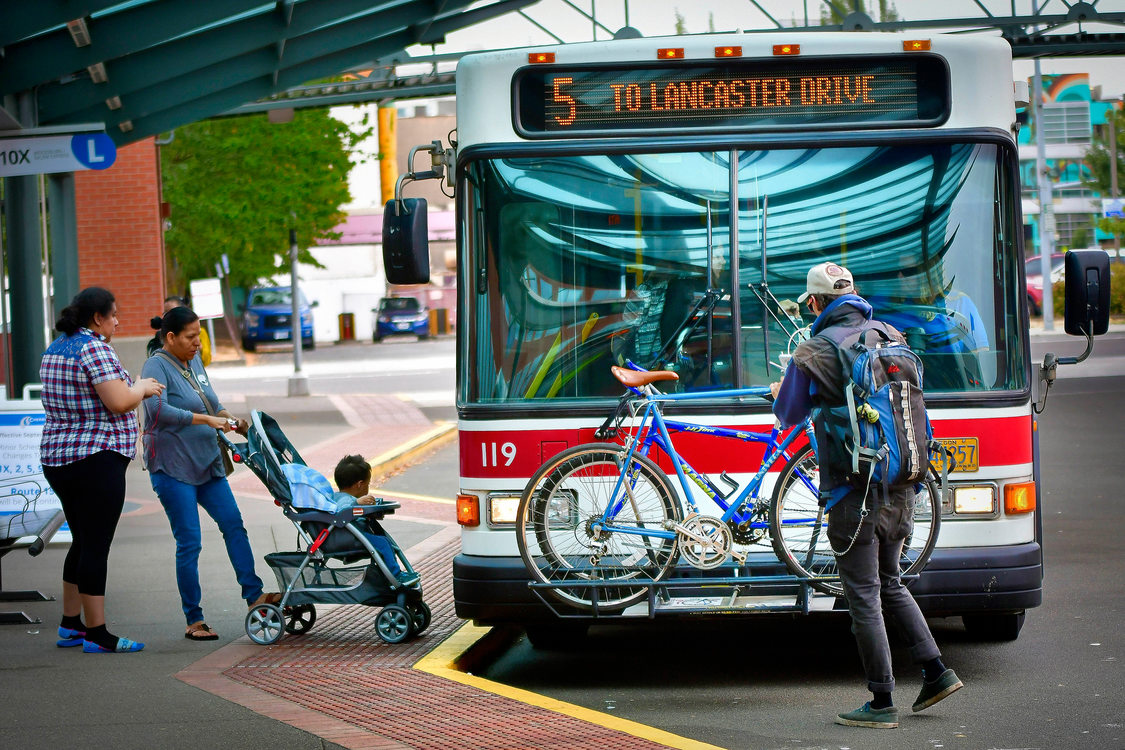 A family boards a Cherriots bus; and a man loads a bike onto the bus' bike rack