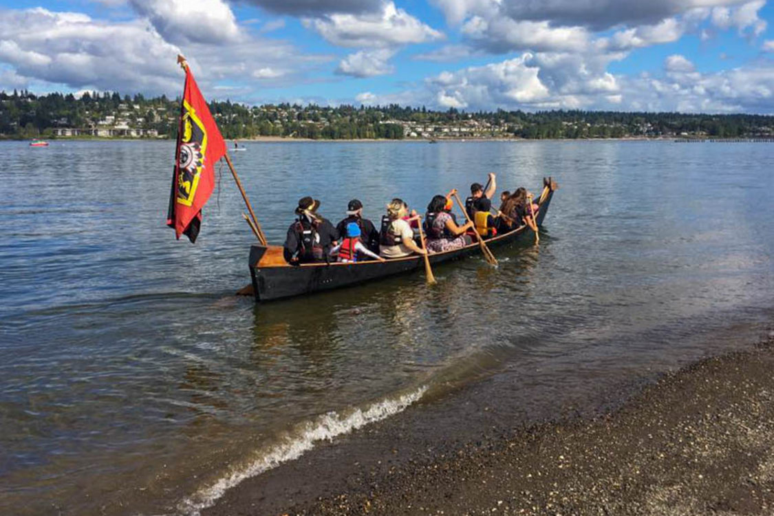The Portland All Nations Canoe Family launches a canoe on a river