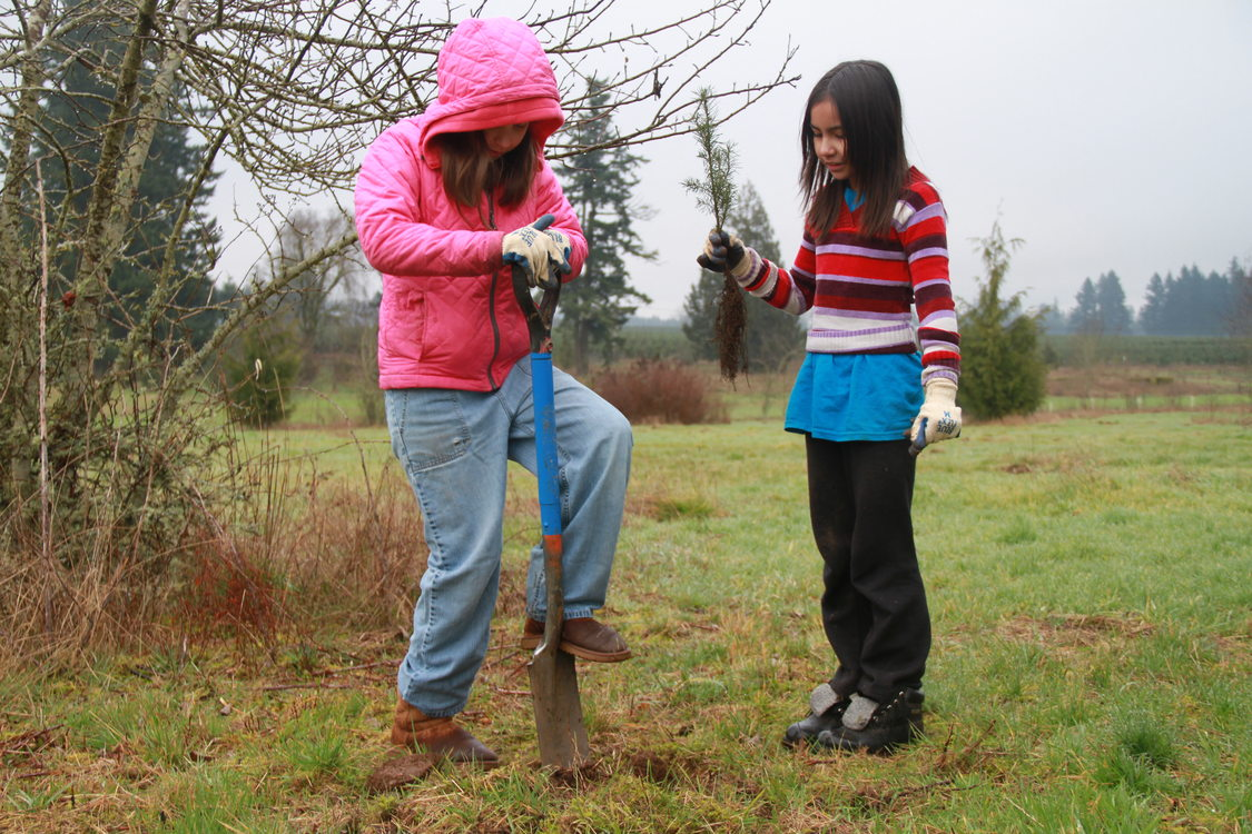 two young girls plant a tree