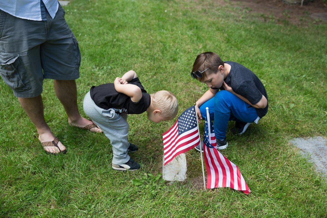 Children look at their grandfathers grave stone on Memorial Day