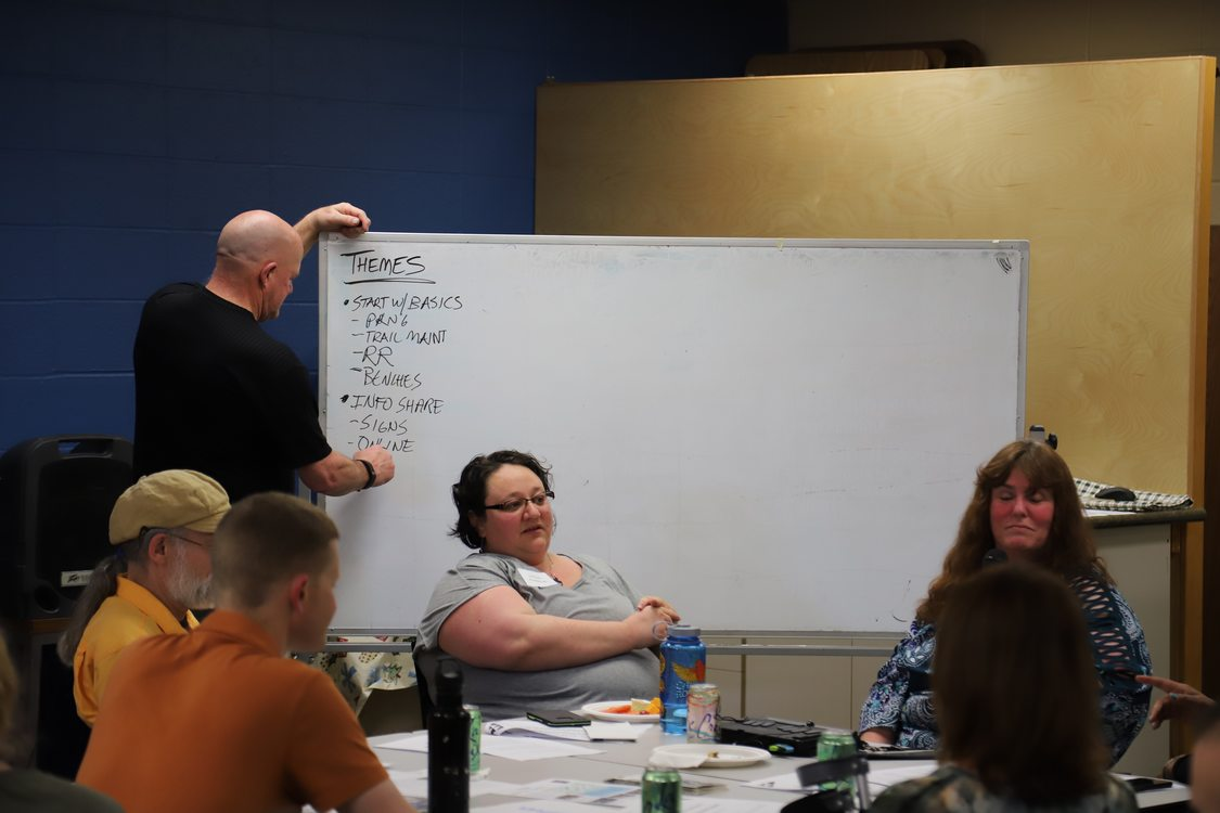 A man takes notes on a white board while community members discuss