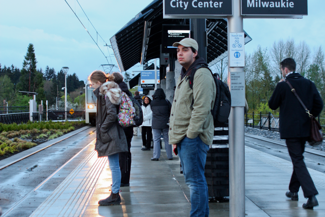 A photo of AJ Romero-Gemmell waiting for the train at the Milwaukie/Main St MAX Station.