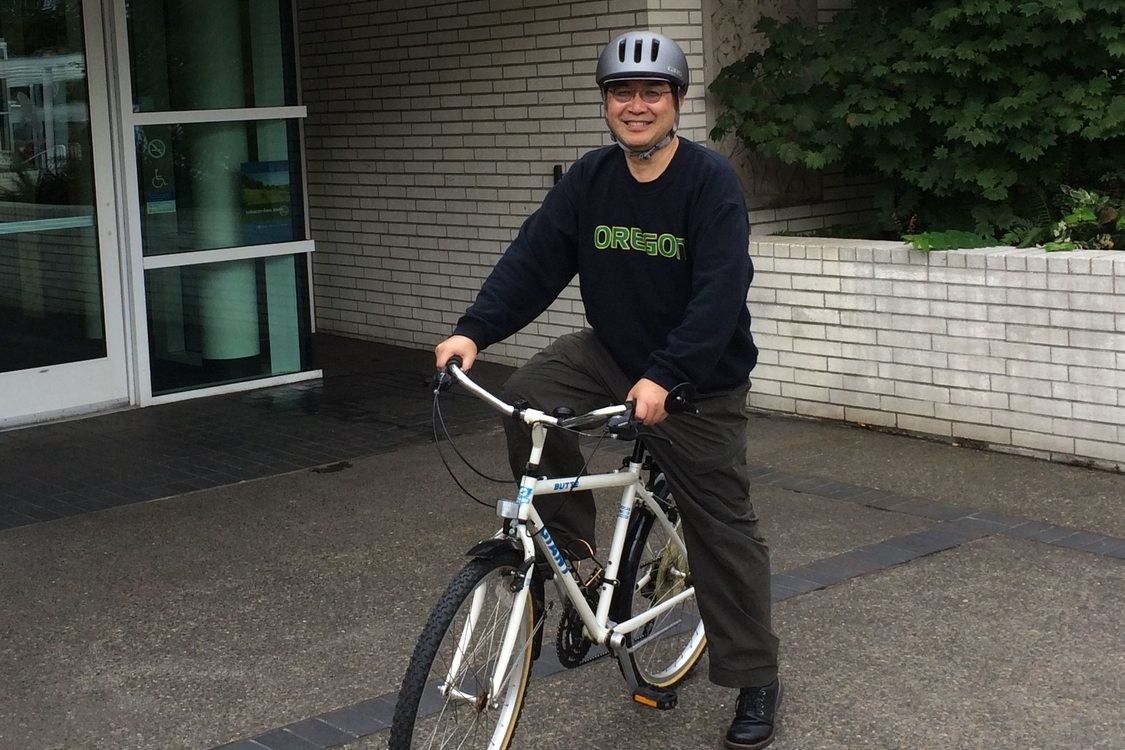 Photo of Mel Huie on a bike in front of the Metro Regional Center