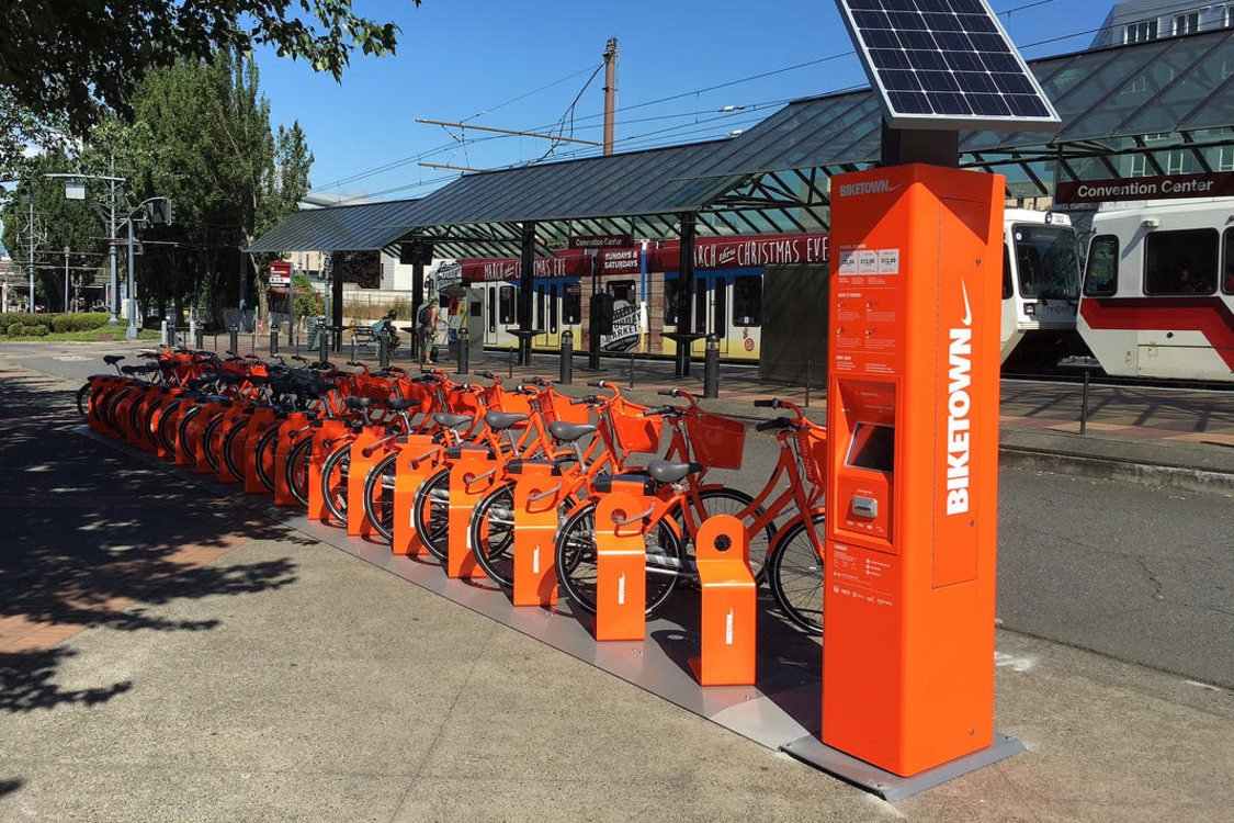 A group of Biketown bikeshare bikes next to a MAX line