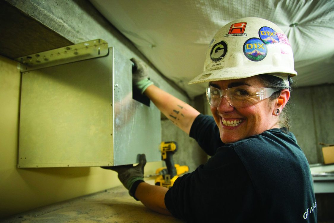 Photo of woman wearing hard hat installing duct work
