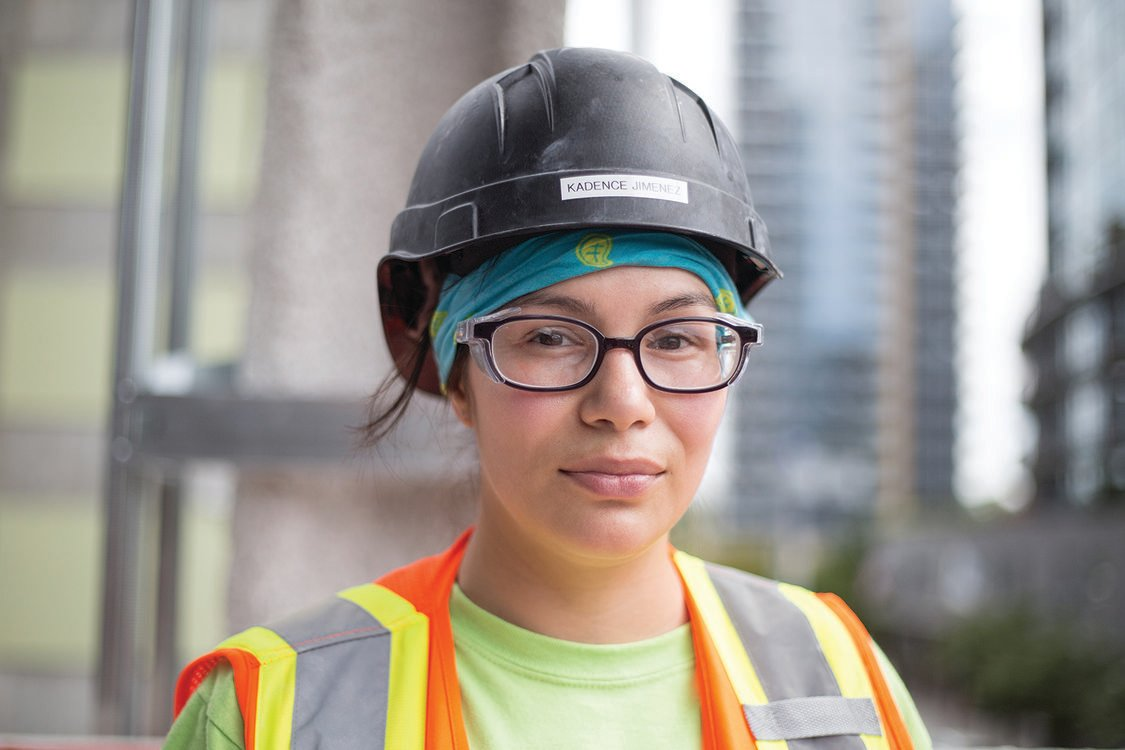 Photo of a woman wearing a hard hat and vest on a construction site
