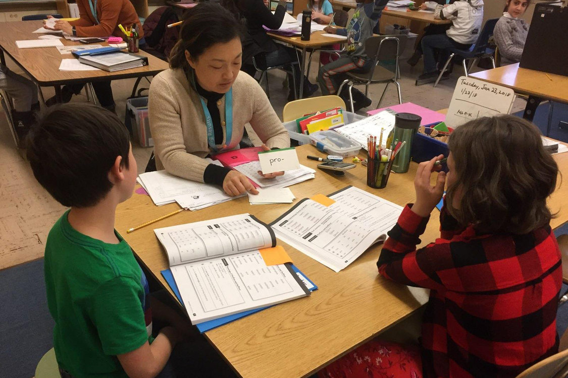 a tutor helps two grade school students with reading