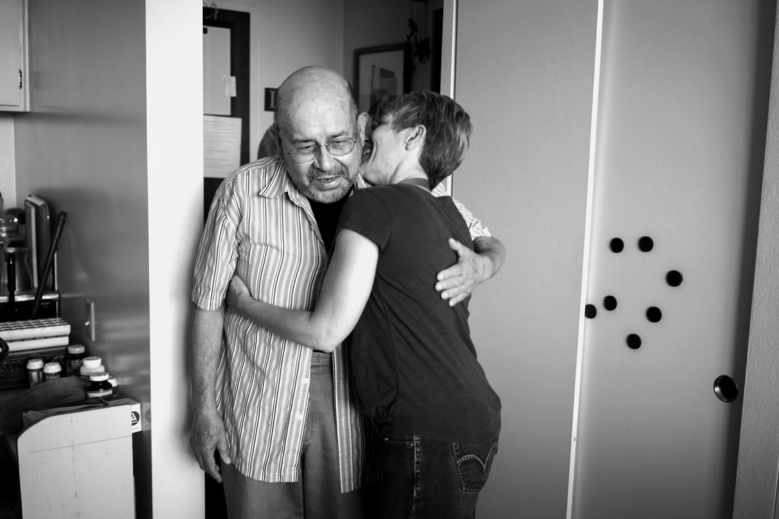 a volunteer gives an elderly client a hug