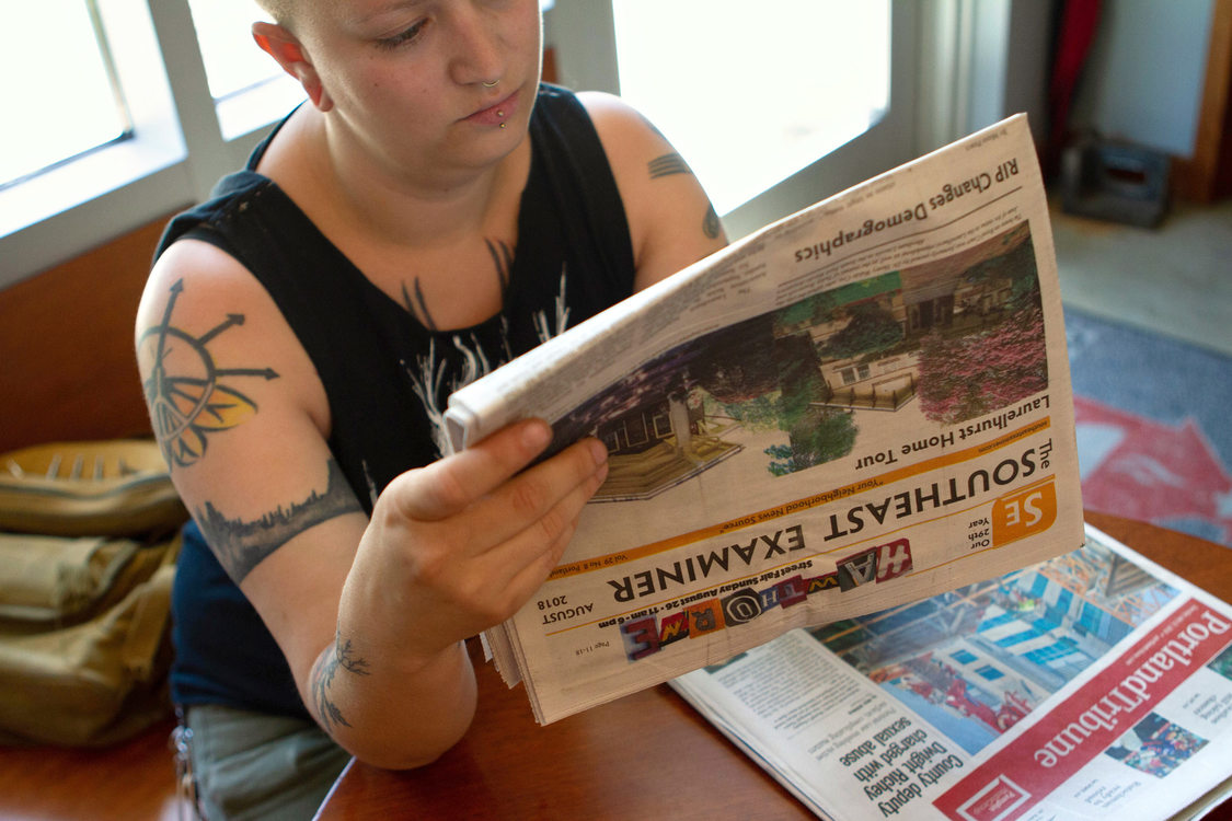 a woman sits in a cafe and reads a newspaper