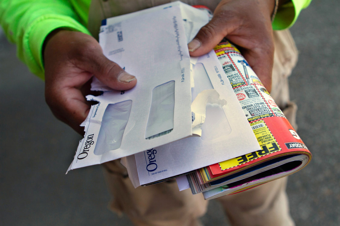 hands hold a stack of opened envelopes and junk mail