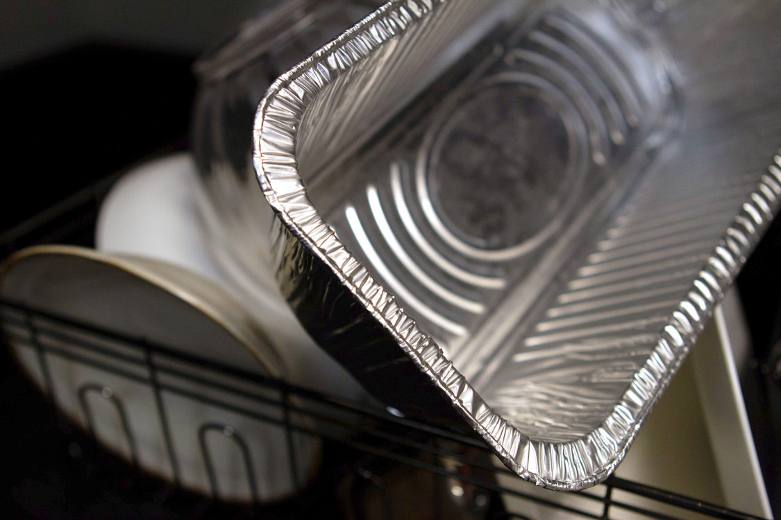 a clean foil serving tray sits in a dish rack
