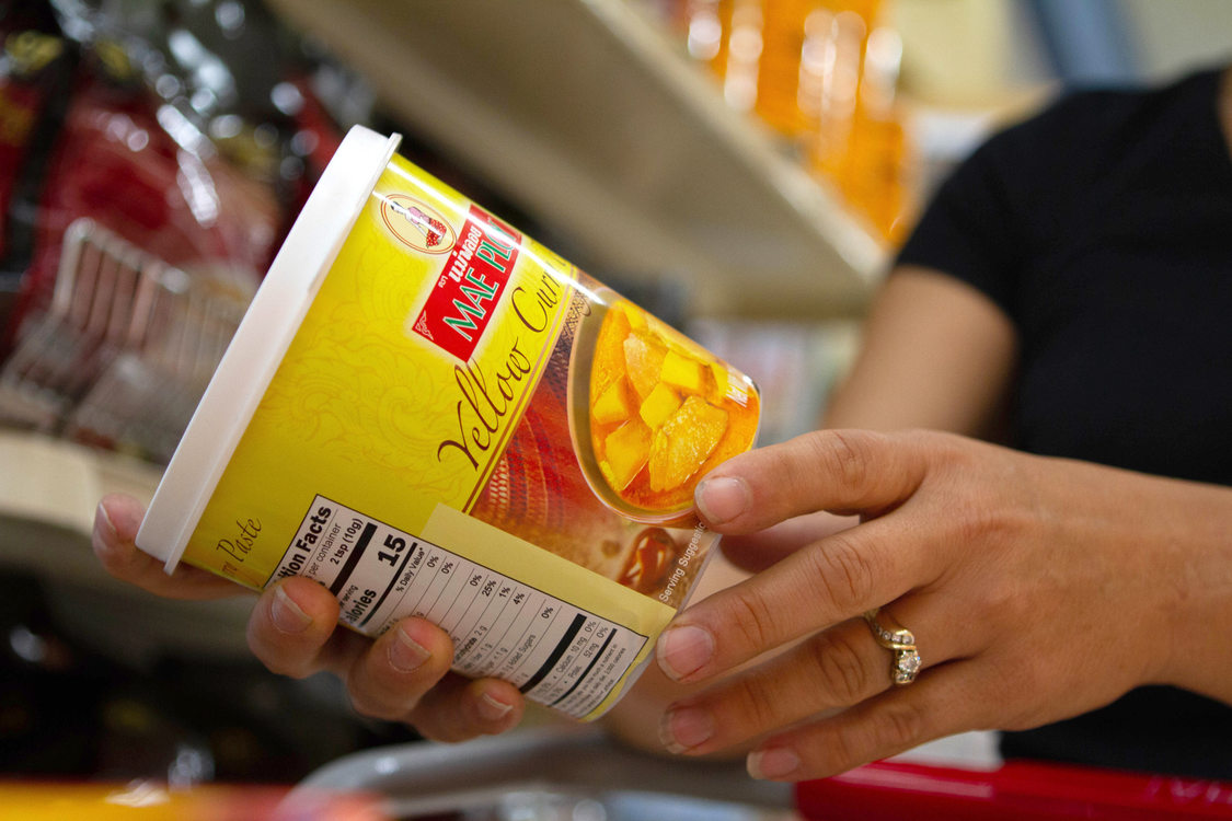 a shopper puts a plastic tub of yellow curry in her shopping cart