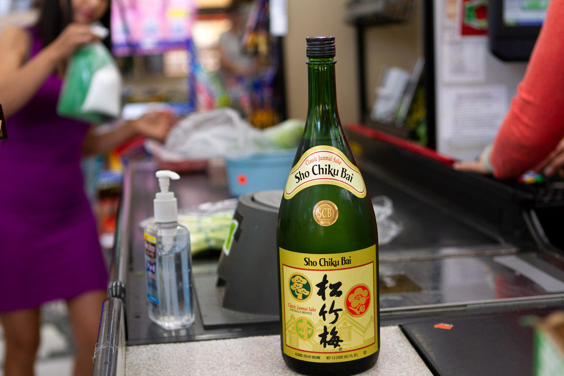 A glass sake bottle gets scanned at a grocery checkout stand