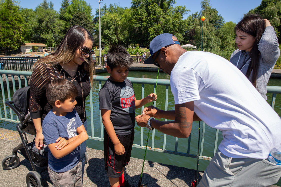 Dishaun Berry of Get Hooked shows a family how to bait their fishing hook at Blue Lake Regional Park.