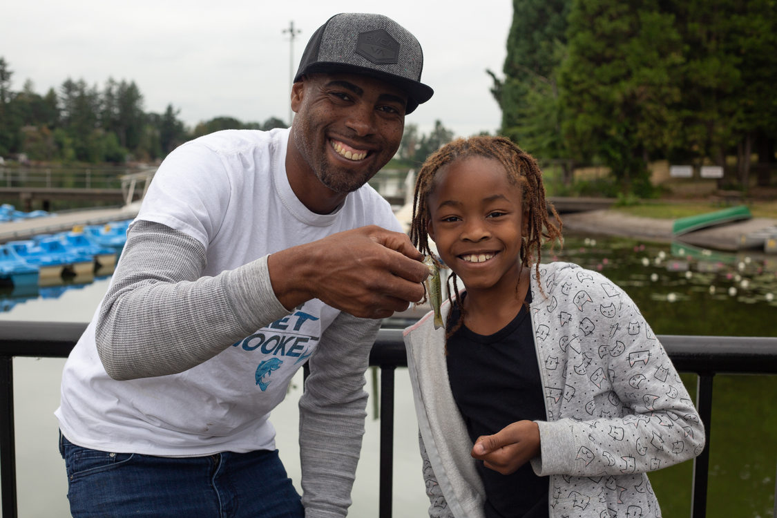 Dishaun Berry of Get Hooked poses with a girl and a fish she caught at Blue Lake Park.
