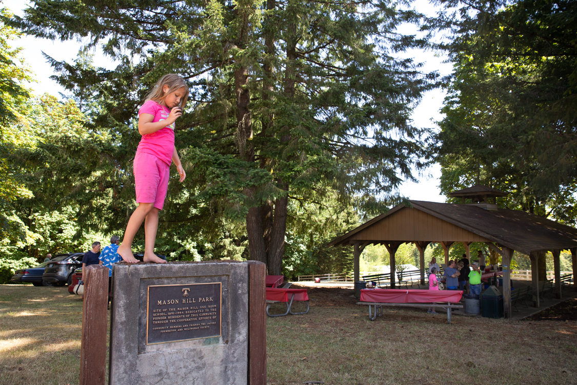 Girl standing on plaque at Mason Hill Regional Park