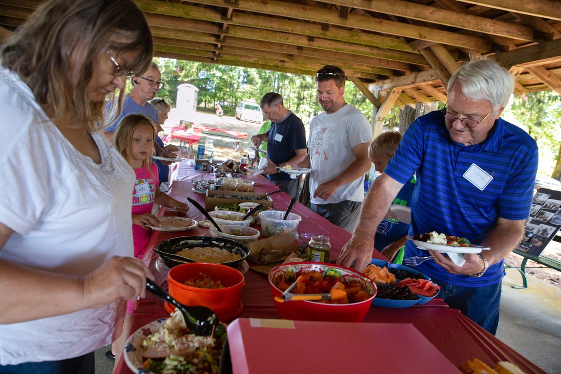 Neighbors filling their plates during a potluck picnic at Mason Hill