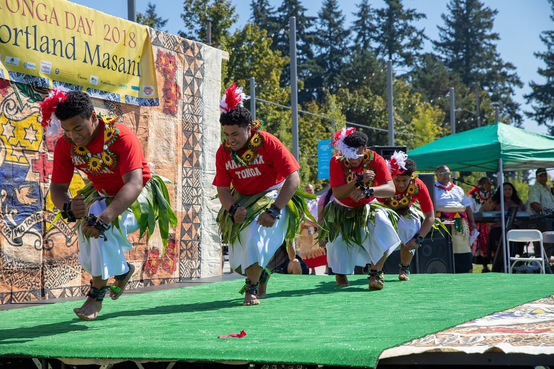 A group of Tongan dancers land from a jump