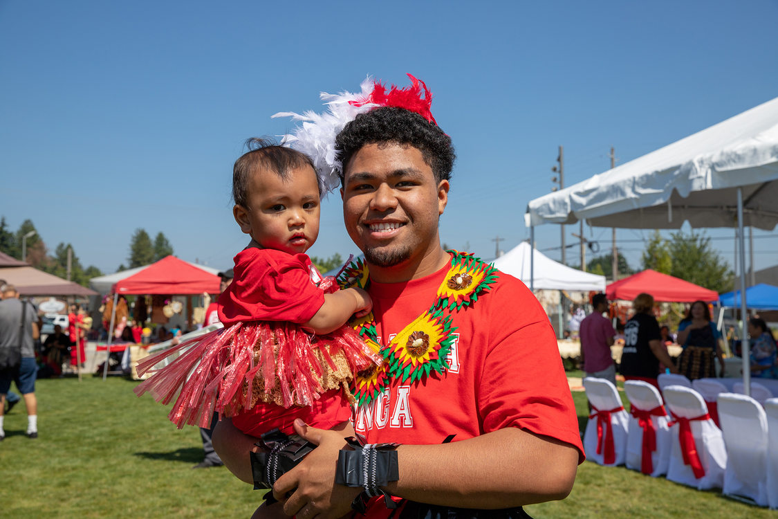 A young Tongan man holds a toddler
