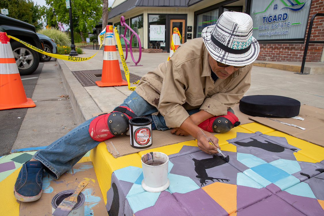 A man paints a mural on the sidewalk in Tigard