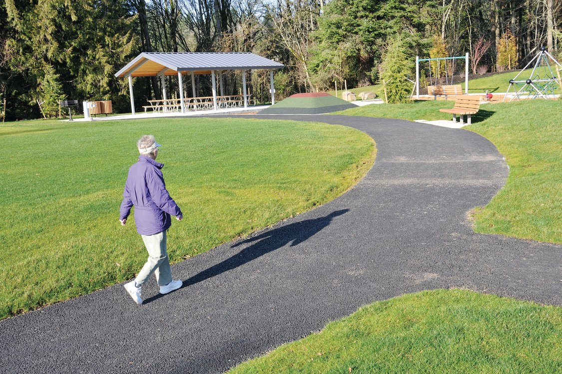Photo of woman walking on paved path in park