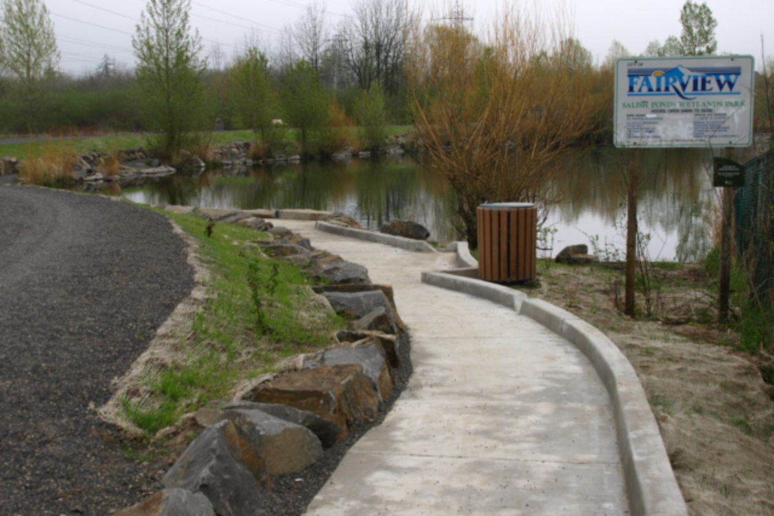 Photo of paved trail with pond in background