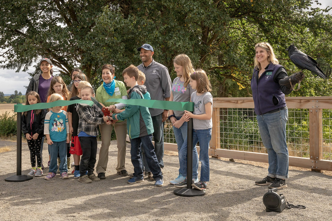 Metro councilor Kathryn Harrington and director of parks and nature, John Blasher invite children from the audience to join them as they cut the ribbon on opening day at Killin Wetlands Nature Park.