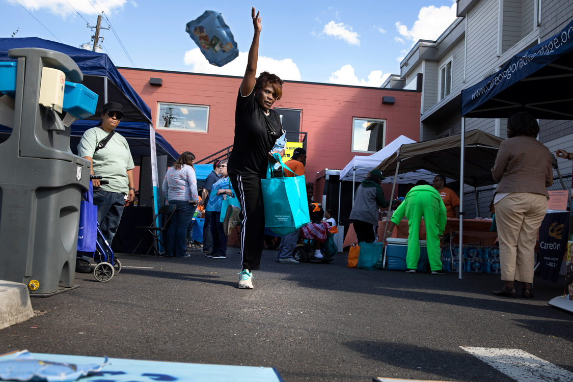 a woman tosses a bean bag in a game of garbage and recycling corn hole