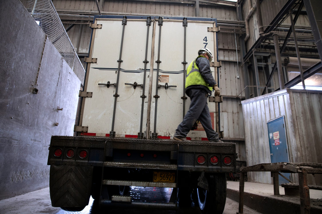 A man in a hard hat closes the back of a truck trailer