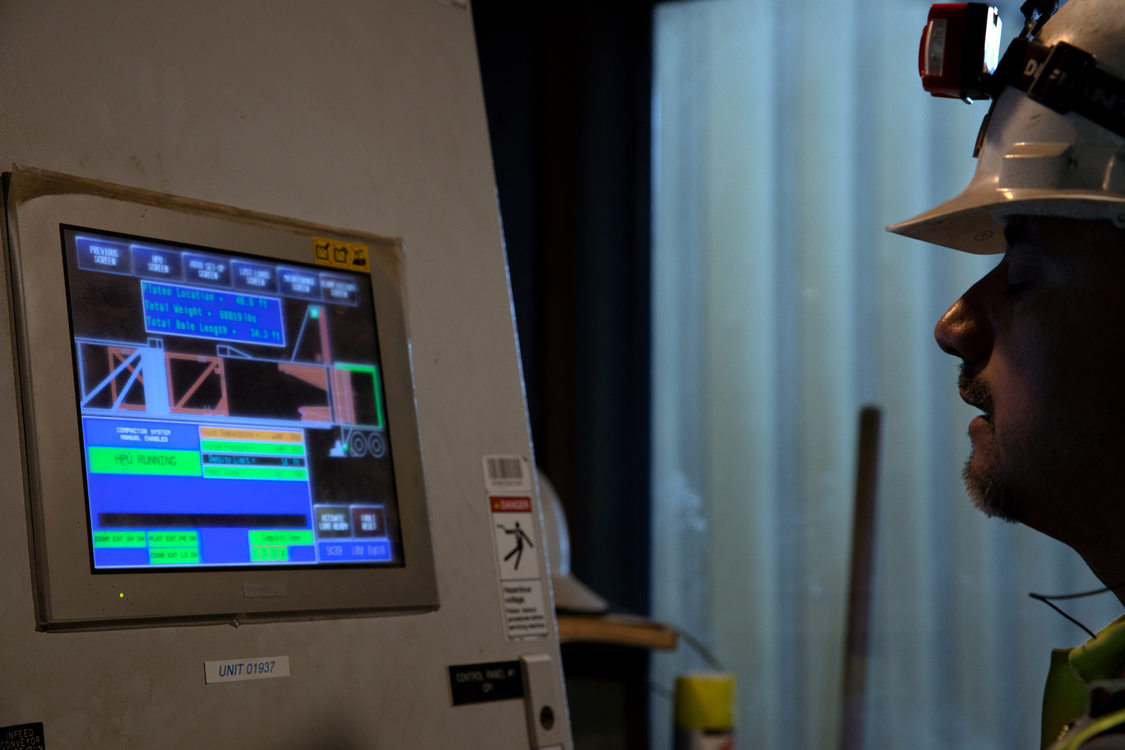a man in a hard hat monitors a computer screen