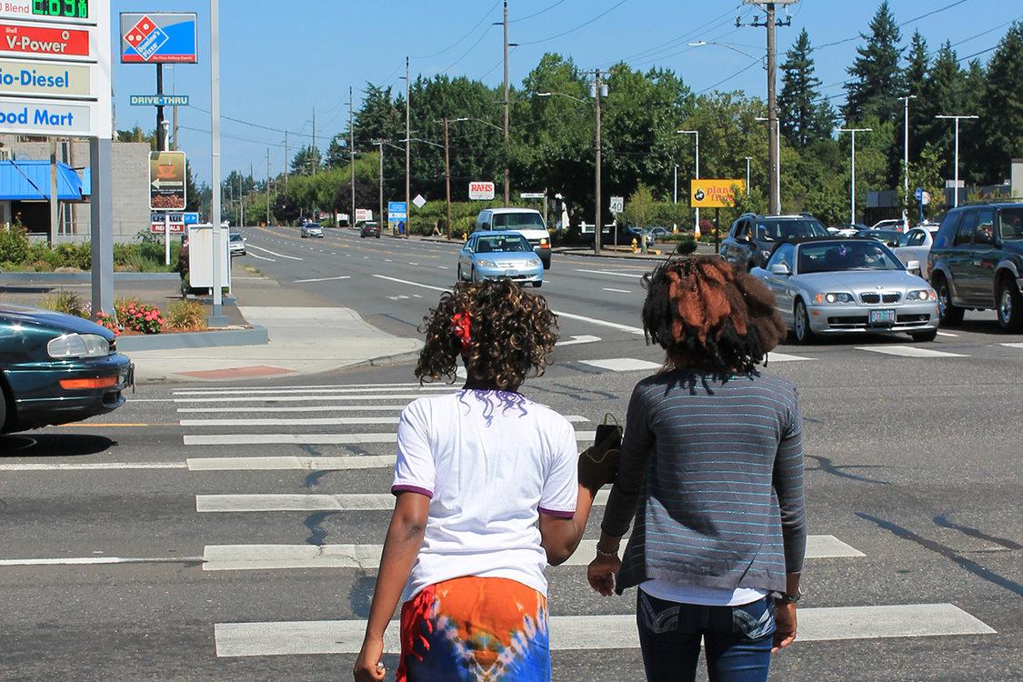Teens walk across a busy street