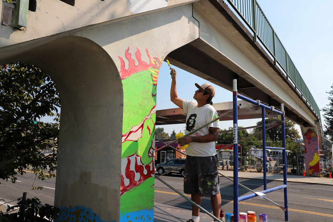 a man paints a mural on the column of a bridge