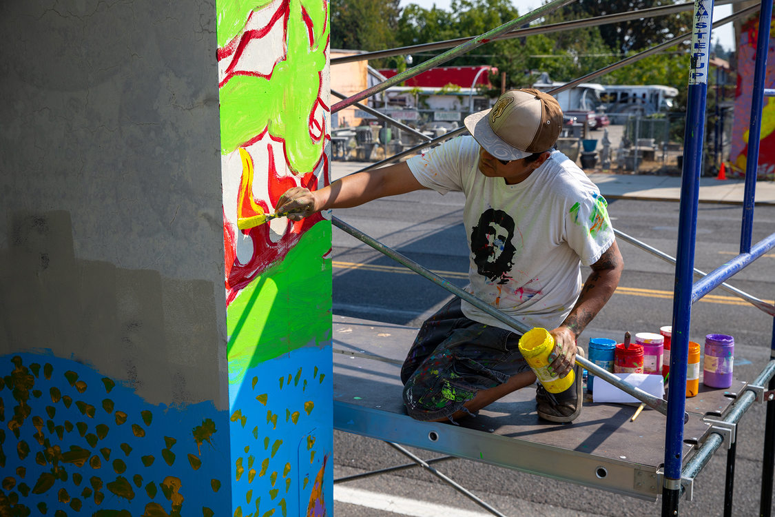 Local artist Rodolfo Redstone Serna paints a mural on the column of a bridge.