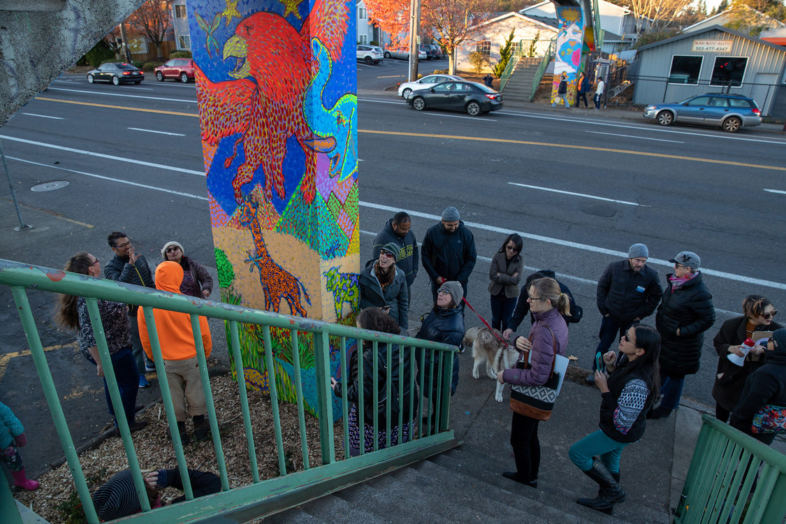 People crowd at the base of a bridge column to check out new mural paintings.