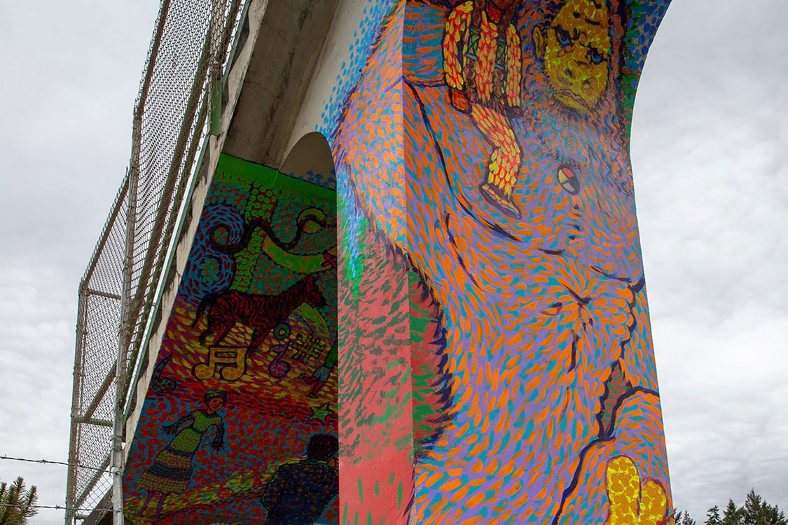 a colorful Bigfoot painted on the column of a pedestrian bridge