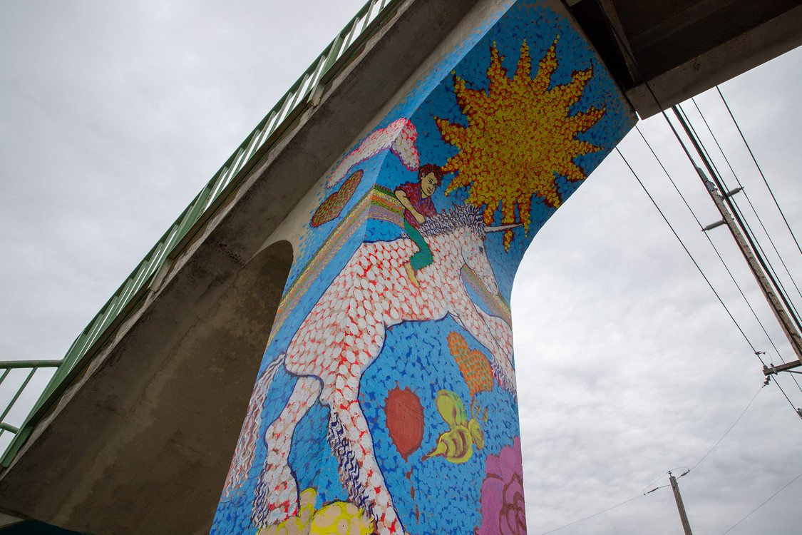 mural painting of a child riding a unicorn; the painting is on the column of a pedestrian bridge